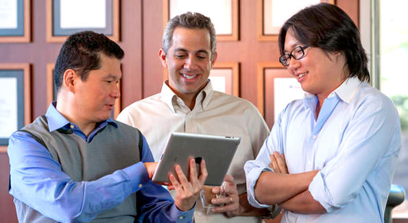 3 people looking at a tablet